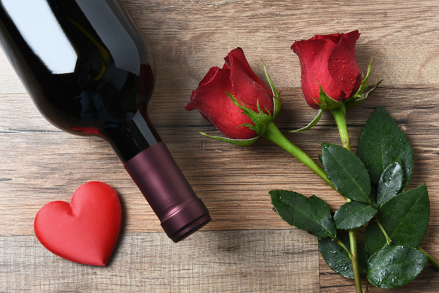 A wine bottle and two red roses and heart on a rustic wood table. Overhead view in horizontal format. Valentines Day Concept.  | Just Wine